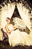 stock photo of wedding arch  - Charming elegant bride under the wedding arch - JPG