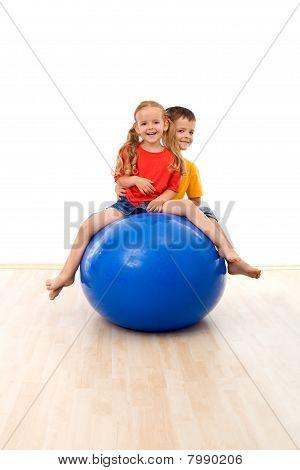 Crianças se divertindo e exercícios com uma bola grande