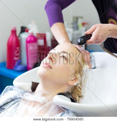 Hairdresser salon. Woman during hair wash.