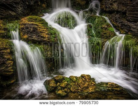 Beautiful motion blurred waterfall flowing from mossy rocks
