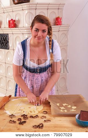 Young Bavarian girl in dirndl stands biscuits from a dough.