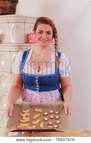 Young girl with a baking tray full of cookies