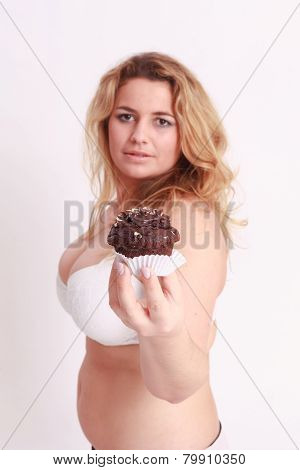 Woman with big breasts presents a muffin chocolate
