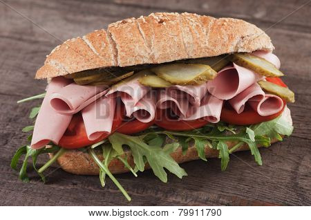 Submarine sandwich with bologna sausage, pickles, tomato and rocket salad