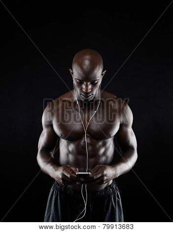 Shirtless Young Man Listening Music On Mobile Phone