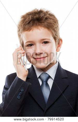Little smiling child boy in business suit hand holding mobile phone or talking smartphone white isolated