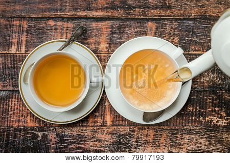 Pouring Tea Into White Cup On Wooden Background