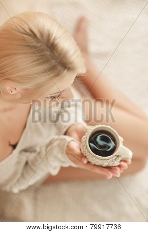 Woman with a cup of coffee in bed.