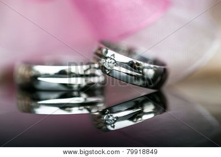 Two splendid wedding rings on a wedding day, shot on a reflective surface. Love concept.
