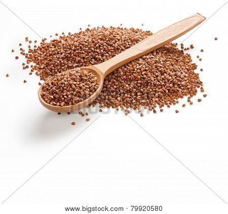 Uncooked buckwheat on wooden spoon