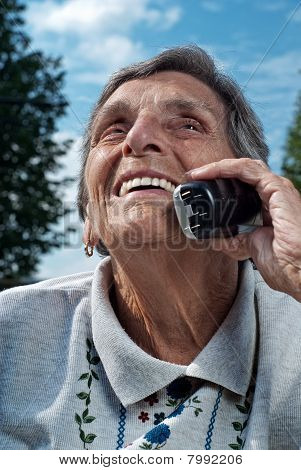 Happy Senior Woman Using Cordless Phone
