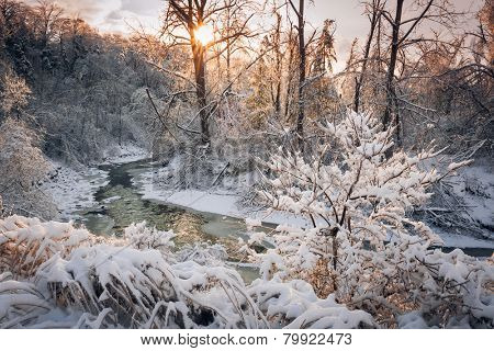Winter landscape of snow covered forest with flowing river after winter snowstorm glowing and sparkling in warm sunshine. Ontario, Canada.