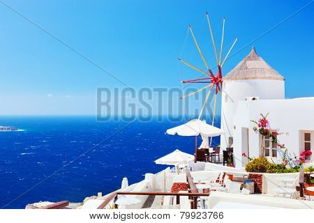 Oia town on Santorini island, Greece. Famous windmills on cliff over the Caldera, Aegean sea.