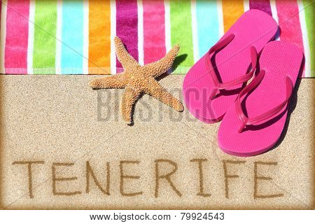 Tenerife beach travel concept background. TENERIFE written in sand with water next to beach towel, summer sandals and starfish. Summer and sun vacation holidays on Canary Islands, Spain.