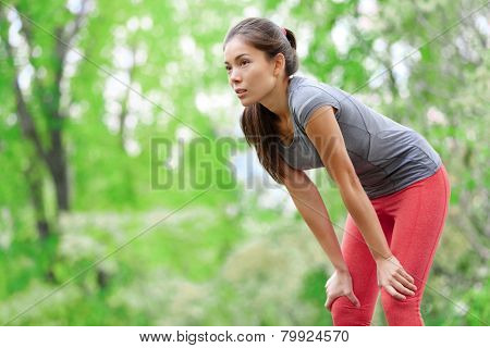 Asian woman athlete runner resting after running and jogging training outdoors in forest. Tired exhausted beautiful sports fitness model living healthy active lifestyle. Mixed race Asian Caucasian.