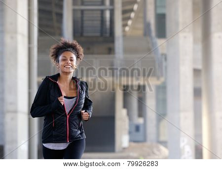 Smiling Young Woman Running Outside