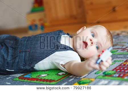 Lovely Baby Boy Playing With Toys At Home. Cute Funny Child Having Fun With Playing. Kid Development