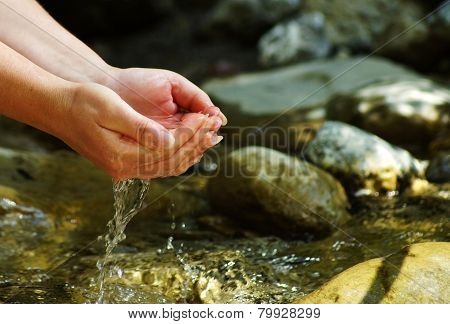 Woman hands on a stream in the Alps
