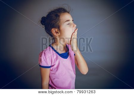 baby girl closes her mouth yawns on gray background