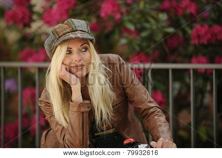 Mature blond woman with bike outdoors in spring smiling