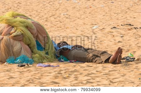 CHENNAI INDIA - FEBRUARY 10: An unidentified man sleeps on the sand near the Marina Beach on Februar