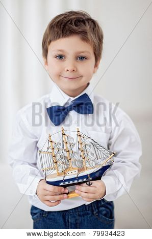 Portrait of cute little boy with ship in his hands