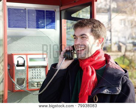 Smiling Young Man Calling From Phone Box