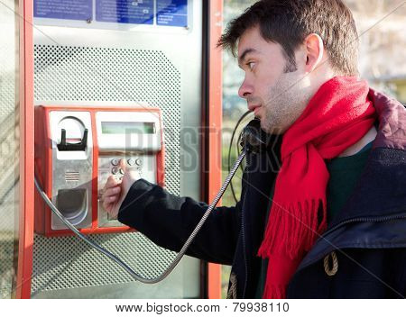 Young Man Dialing Phone Number At Public Phone Box