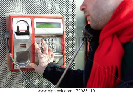 Man Dialing Phone Number On Public Phone