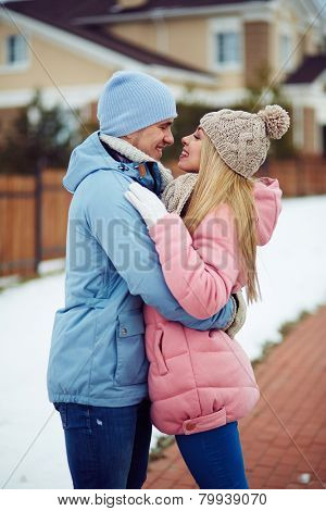 Young dates in winterwear looking at one another in urban environment