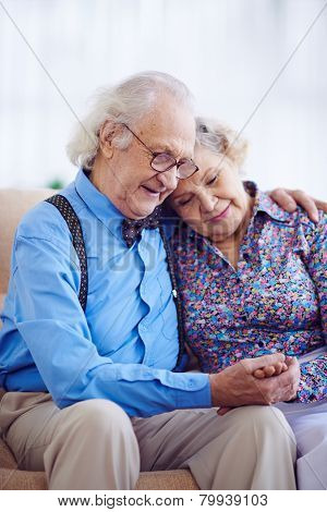 Amorous couple of pensioners in smart clothes