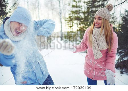 Happy young couple playing snowballs in winter park