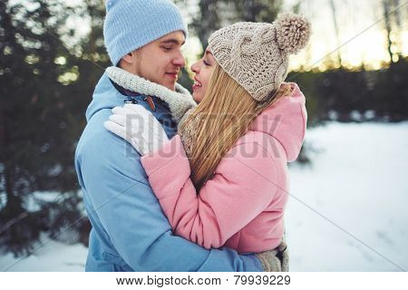 Amorous couple in embrace looking at one another in park