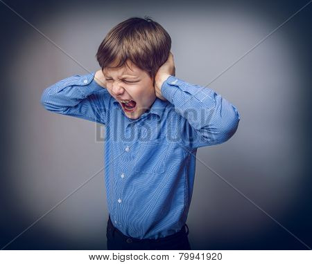 teenager boy closed  ears with his hands on gray background