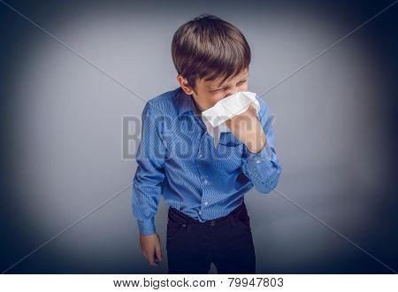 teenager boy of 10 years European appearance sick sneezing