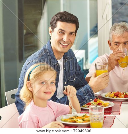 Father and daughter eating salad at lunch with grandfather at home