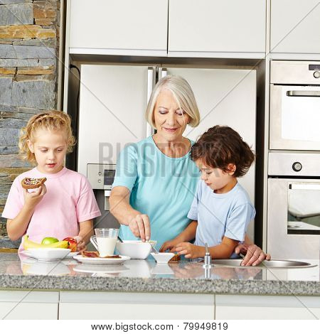 Grandmother preparing a healthy breakfast for her two grandchildren in the kitchen