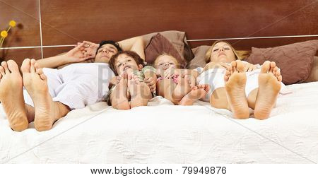 Family with two children laying in bed with their feet forward