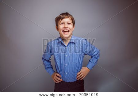 teenager boy rejoices over gray background