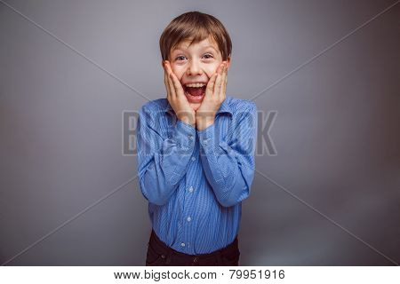 teenager boy surprised a rejoices over gray background