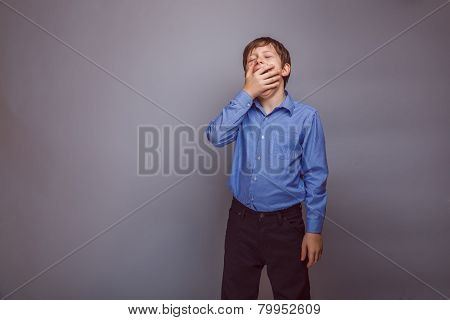 teenager boy yawns on gray background