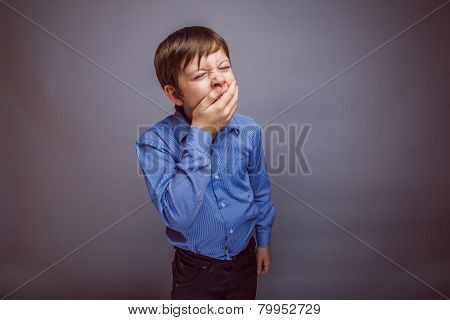 teenager boy yawns wants to sleep on gray background