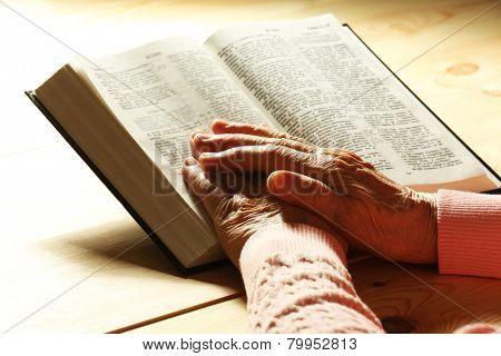 Hands of old woman with Bible on wooden table background