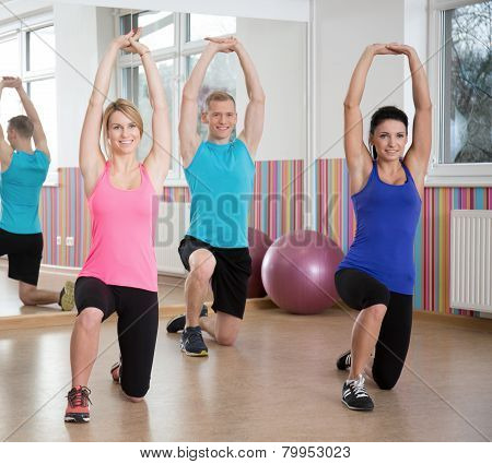 People Exercising In Pilates Class
