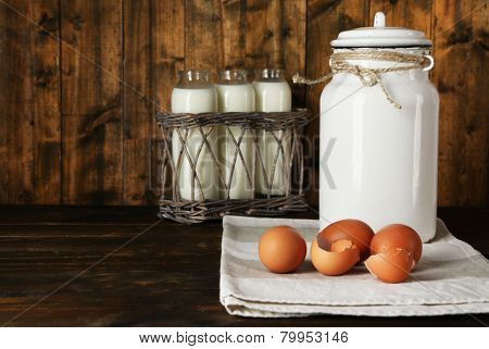 Milk can with eggs, eggshell and  glass bottles on rustic wooden background