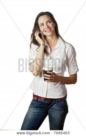 Portrait Of An Attractive Casual Woman Talking On Her Mobile And Holding A Coffee
