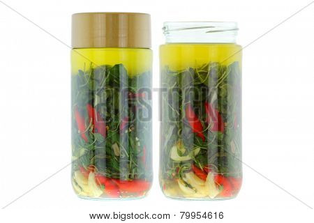 Glass jars full of spicy Olive oil with Thai Basils, Chilies, and Garlic