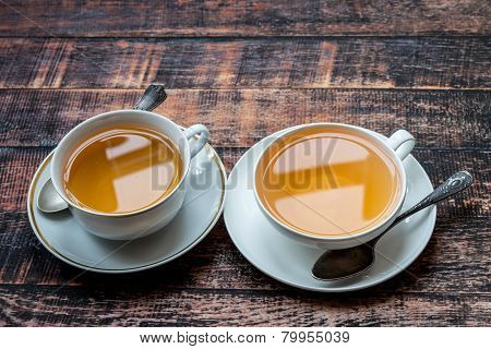 Two Cups Full Of Tea On Old Wooden Table