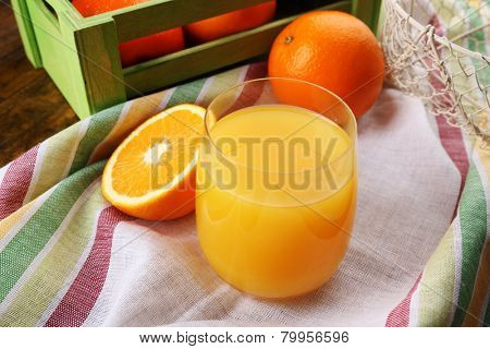 Glass of orange juice with crate on striped fabric and slices on wooden table background