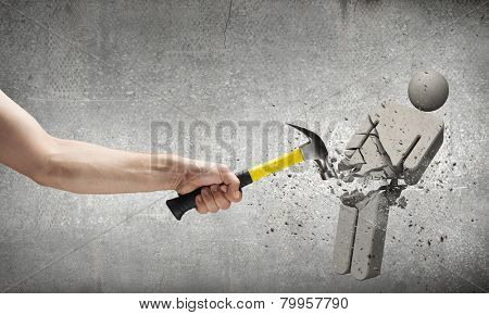 Close up of hammer in human hand breaking stone man figure